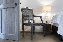 Een grijs geschilderde Franse fauteuil in een slaapkamer van Le Mas, een vakantiehuisje met 5 slaapkamers in de buurt van Monpazier in de Dordogne