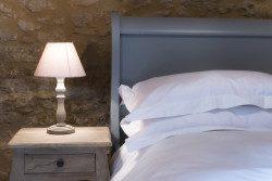 Un lit avec une table de chevet et une lampe dans la chambre du Mazet, un gîte pour un couple en Dordogne.