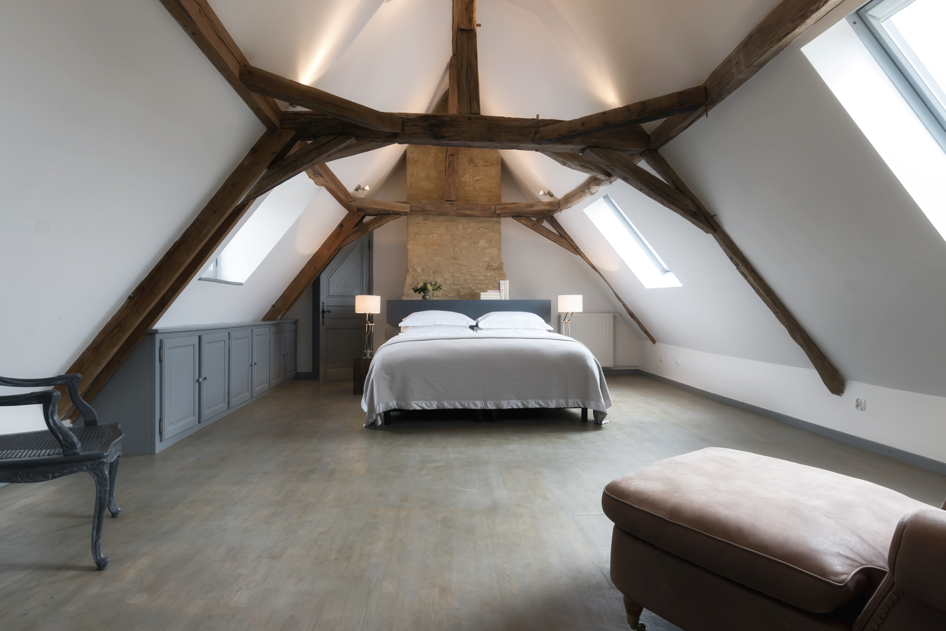 Bedroom 1 of Le Mas, a family holiday home in the Dordogne, with exposed beams, wooden floor, grey painted cupboard and a double bed