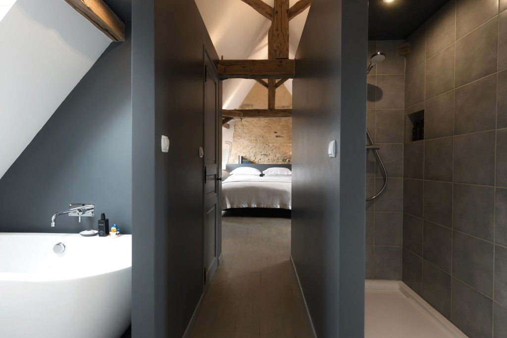 A white bath on the left, and a shower on the right with a corridor leading to Bedroom 2 in Le Mas, a renovated farmhouse for rent near Monpazier in the Dordogne