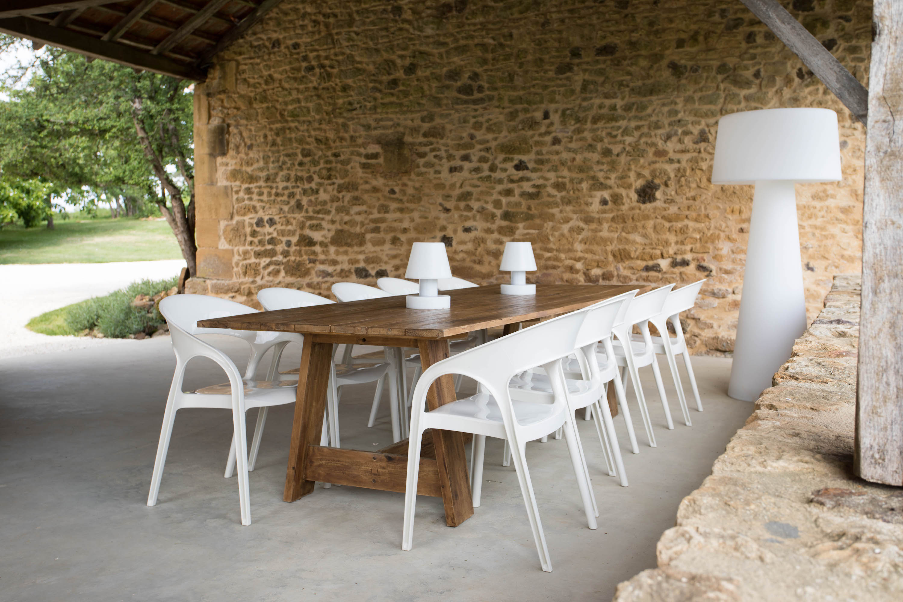 A wooden table with Pedrali chairs and outdoor lamp in the summer kitchen of Le Mas, a 5-star holiday home in the Dordogne, France