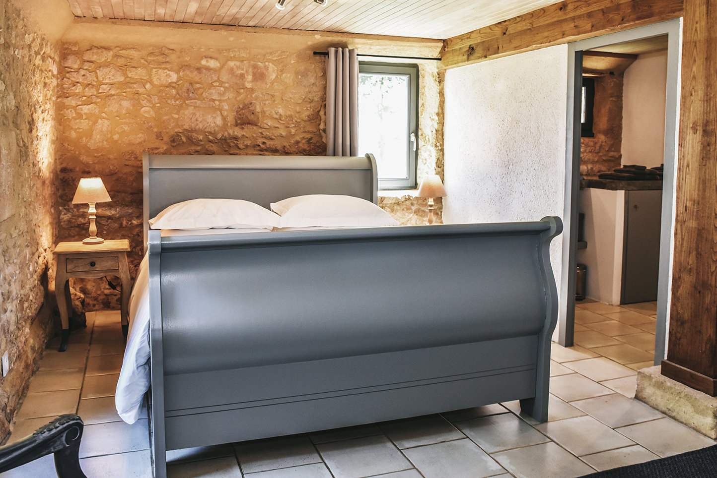 A double bed in a bedroom with a door leading to an en suite bathroom in Le Mazet, a holiday cottage in the Périgord