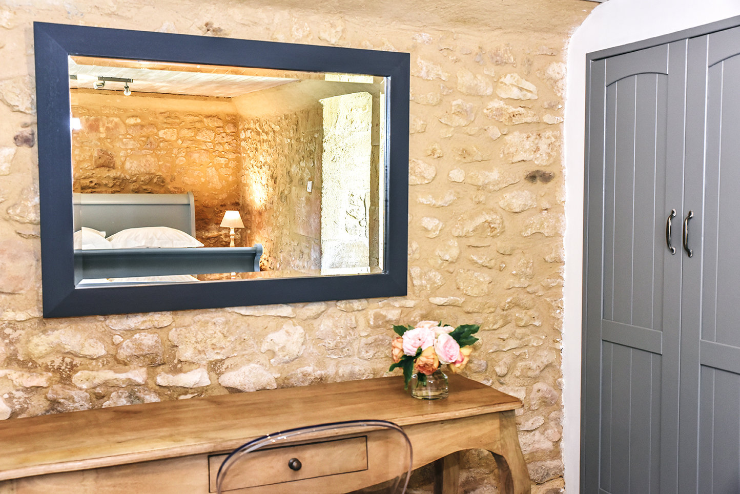 A view in a mirror on a stone wall of the lower ground floor bedroom of Le Mazet, a holiday cottage in the Dordogne
