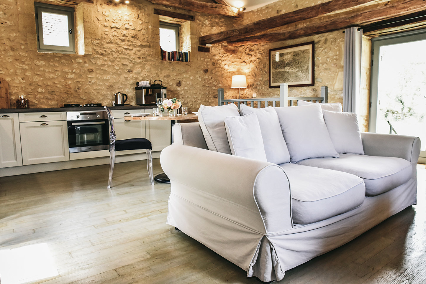 A grey sofa and open kitchen on the upper ground floor of Le Mazet, a charming cottage for rent in the Dordogne