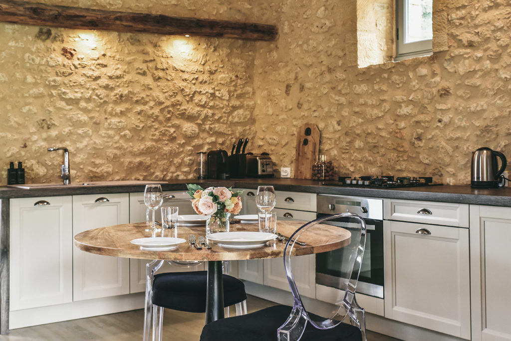A table and Pedrali chairs in an open kitchen of Le Mazet, a charming cottage for rent in the Dordogne, France