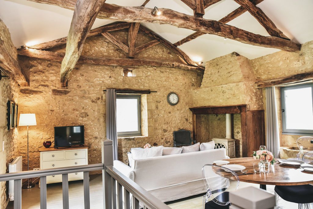 A sitting room with a table and Pedrali chairs, a sofa, a wood burner, stone walls and exposed beams in Le Mazet, a rental cottage for a couple in the Dordogne