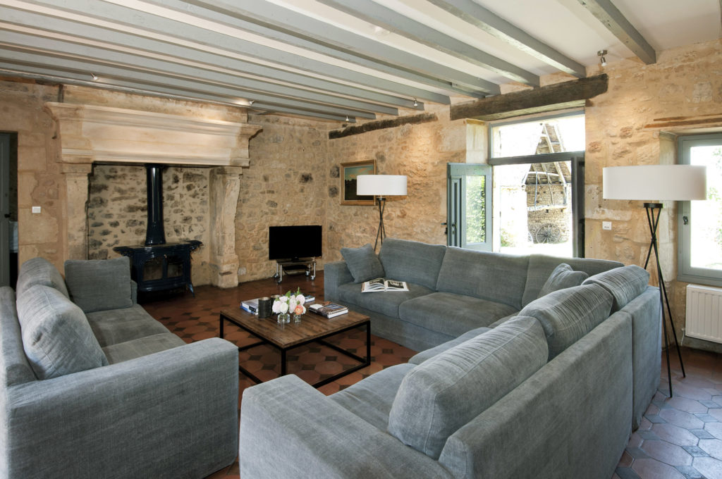 A sitting room with large fireplace, blue sofas and painted grey beams in Le Mas, a luxury holiday accommodation in the Dordogne