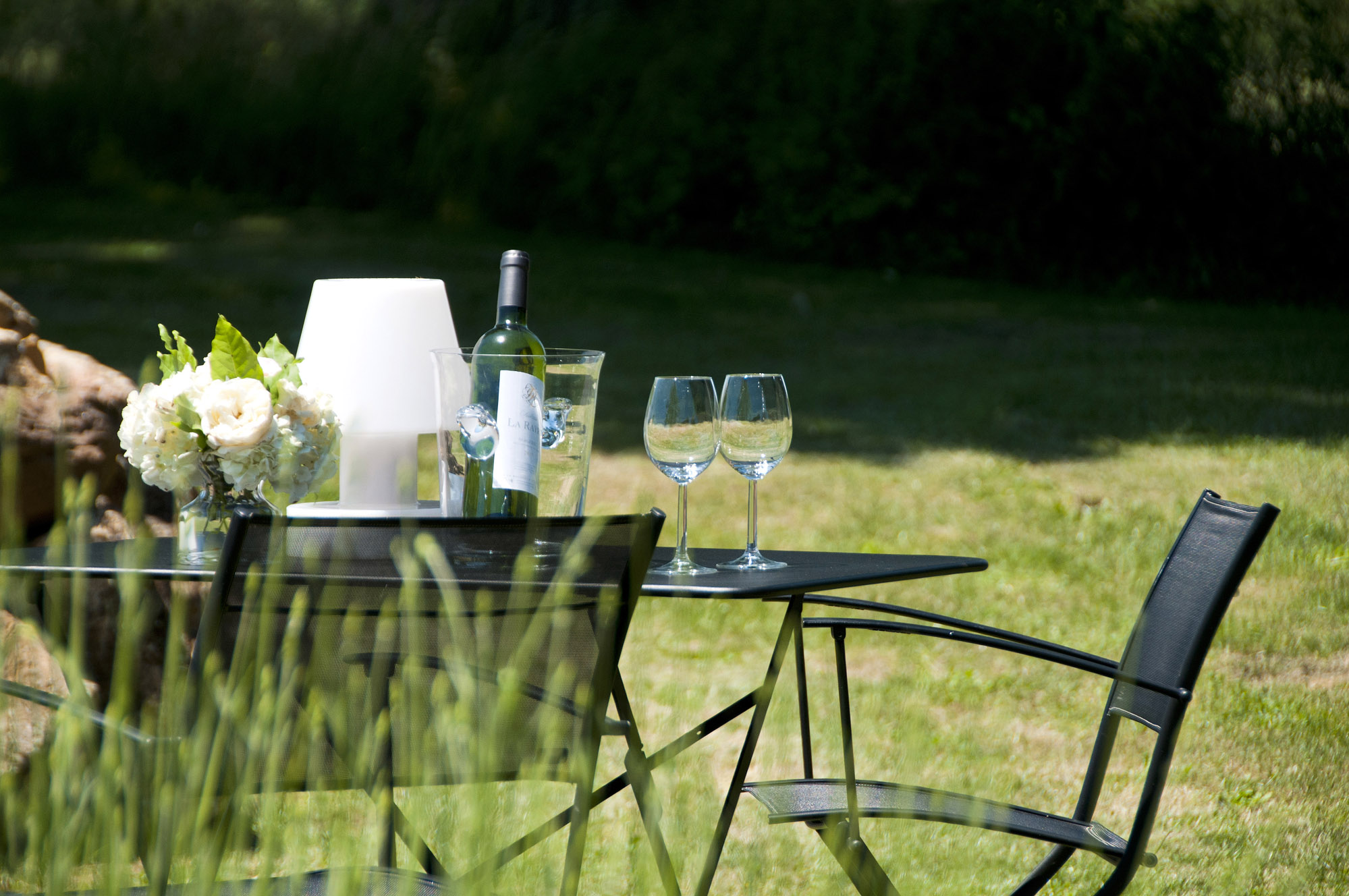Fermob black table and chairs in the verdant garden of Le Mazet, a bolthole in the Dordogne