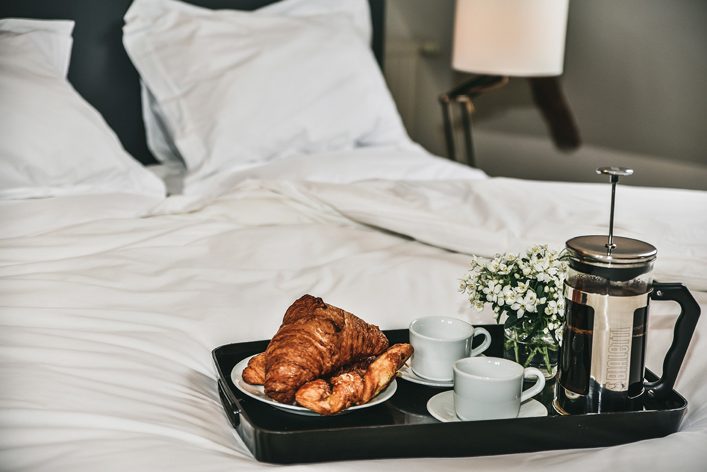 A tray with croissants on coffee placed on crisp white Egyptian cotton sheets in a bedroom in Le Mas, a luxury holiday rental in the Dordogne