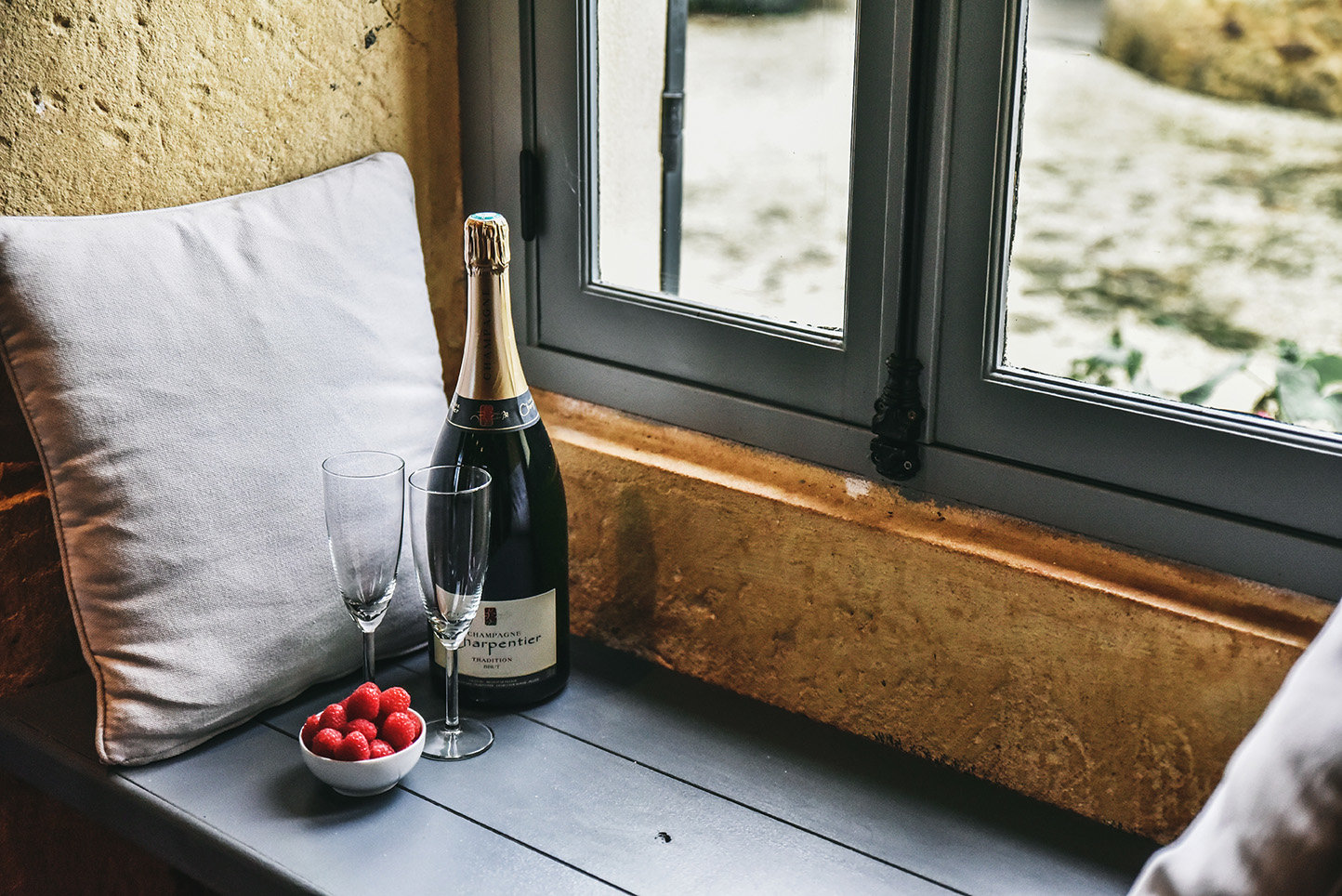 Champagne, glasses and raspberries on the window-seat in the kitchen of Le Mas, a 5-star holiday home in the Dordogne, France