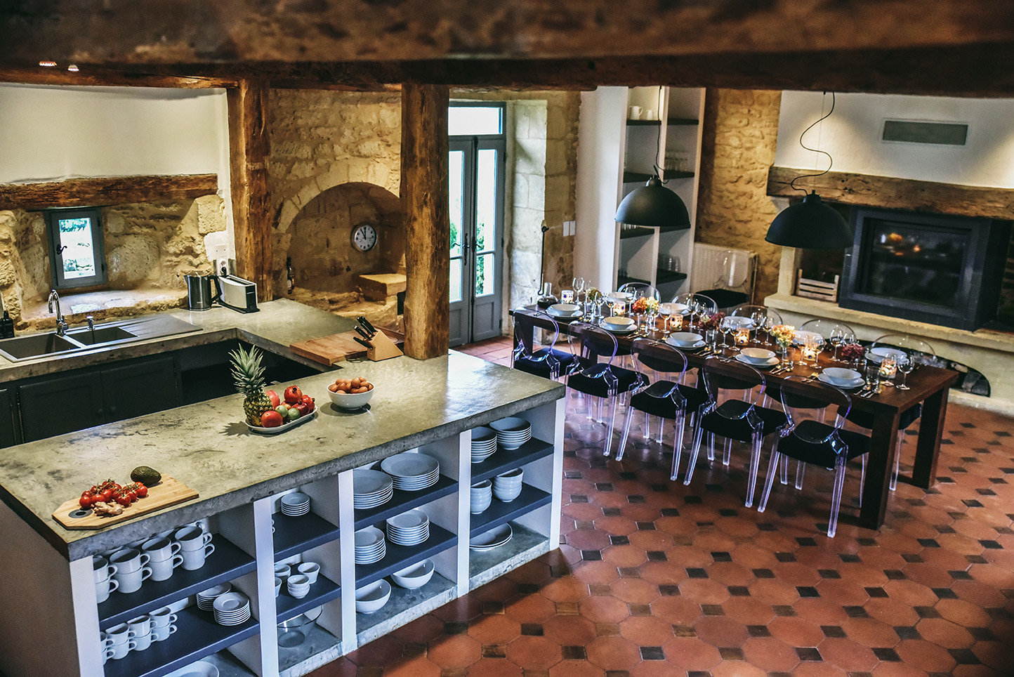 A spacious and well-equipped kitchen with terracotta tiled floor, a table and Pedrali chairs and a fireplace at Le Mas, a characterful holiday home in the Dordogne, France