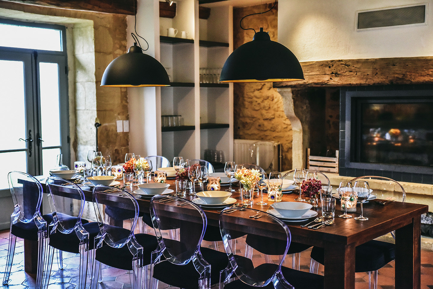 The table laid for dinner in front of a fireplace in Le Mas, a luxury holiday home in the Dordogne