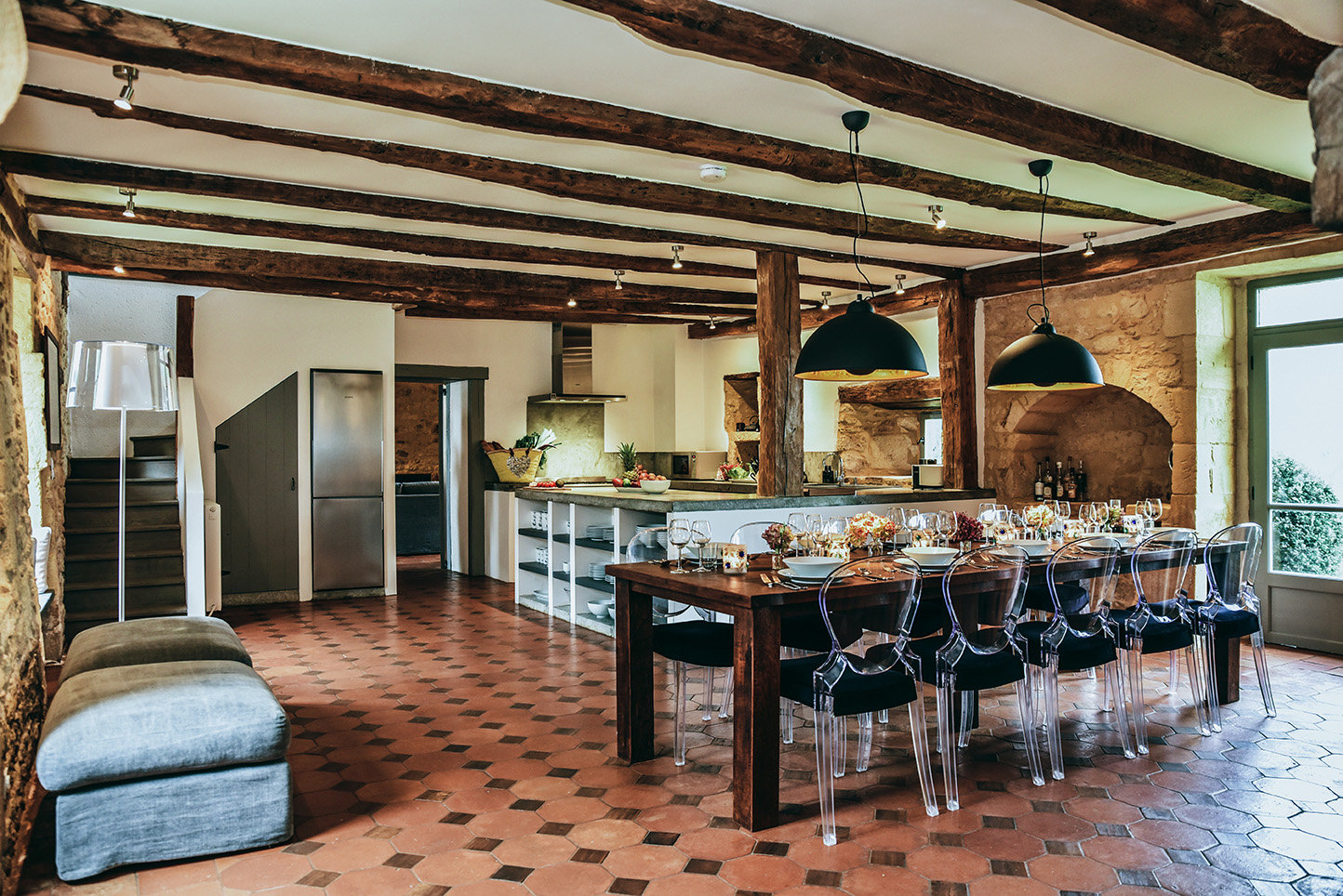 The kitchen of Le Mas, a 5-star holiday home in the Dordogne, with table, perspex Pedrali chairs, and a terracotta floor