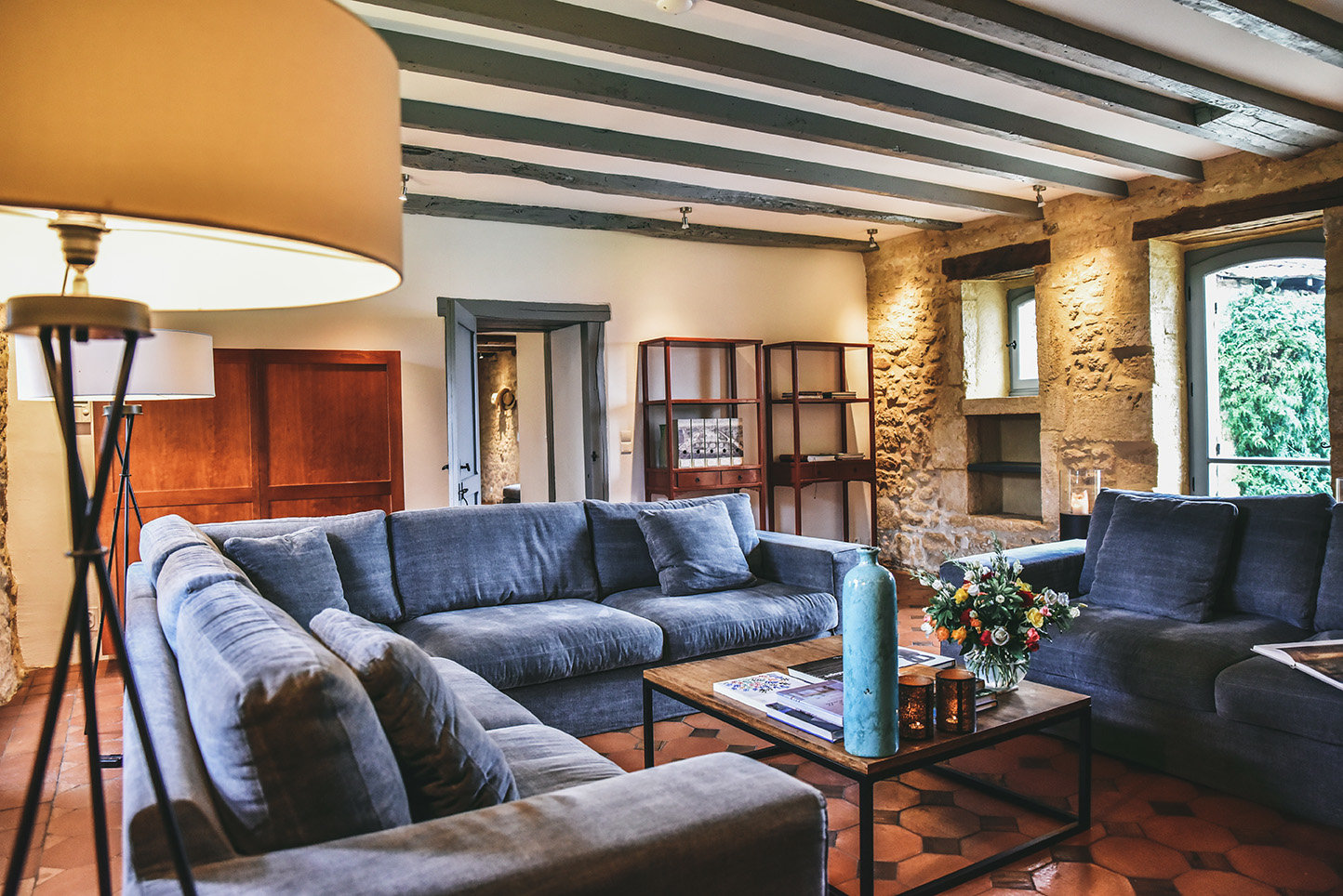 The sitting room of Le Mas, a beautiful holiday rental in the Dordogne, with stone walls, a terracotta tiled floor, blue sofas and a DePadova Shigeto cherrywood cupboard