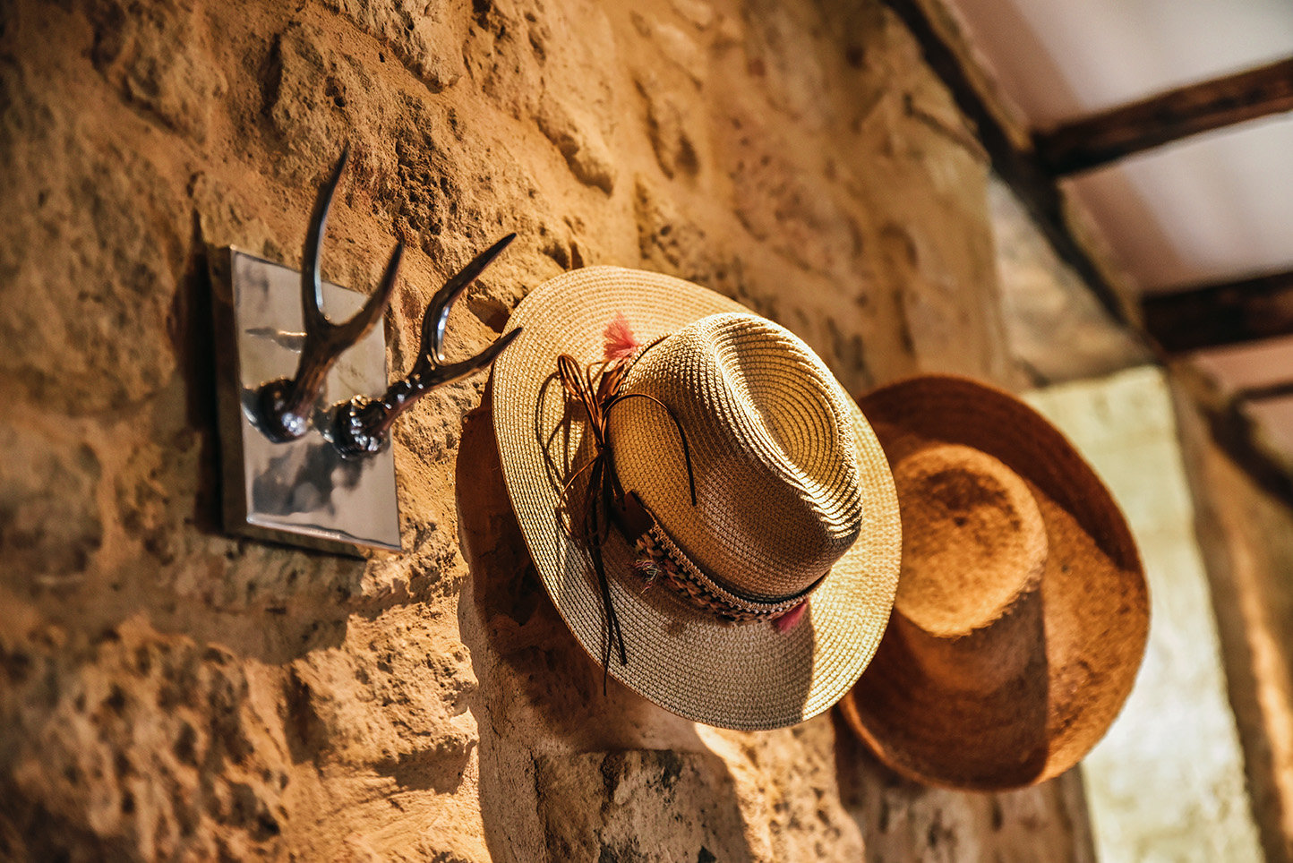 Summer straw hats hanging on silver-coloured antler hooks made by Pols Potten on a stone wall in the kitchen of Le Mas, a holiday rental in the Dordogne