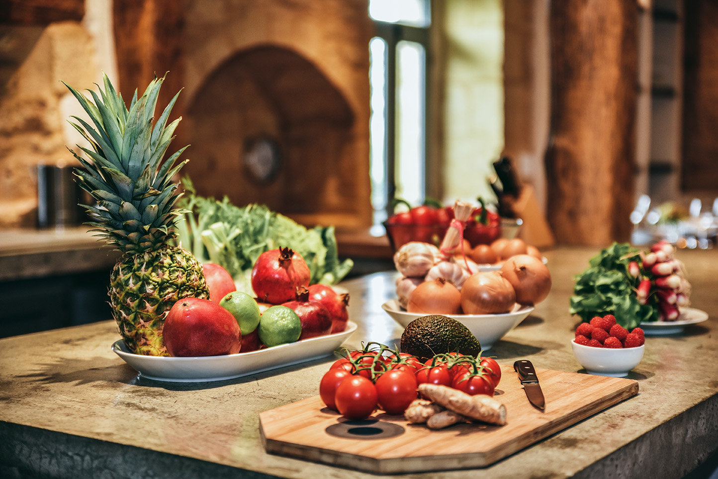Fresh fruit and vegetables from the market on the concrete kitchen island in Le Mas, a Dordogne farmhouse which can accommodate up to 10 people