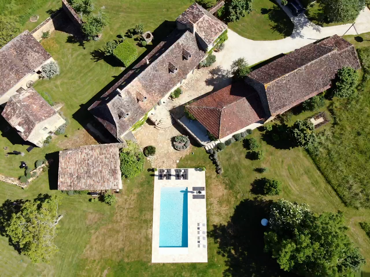 An aerial shot of Le Mas & Le Mazet in the Dordogne with centuries-old buildings and a swimming pool