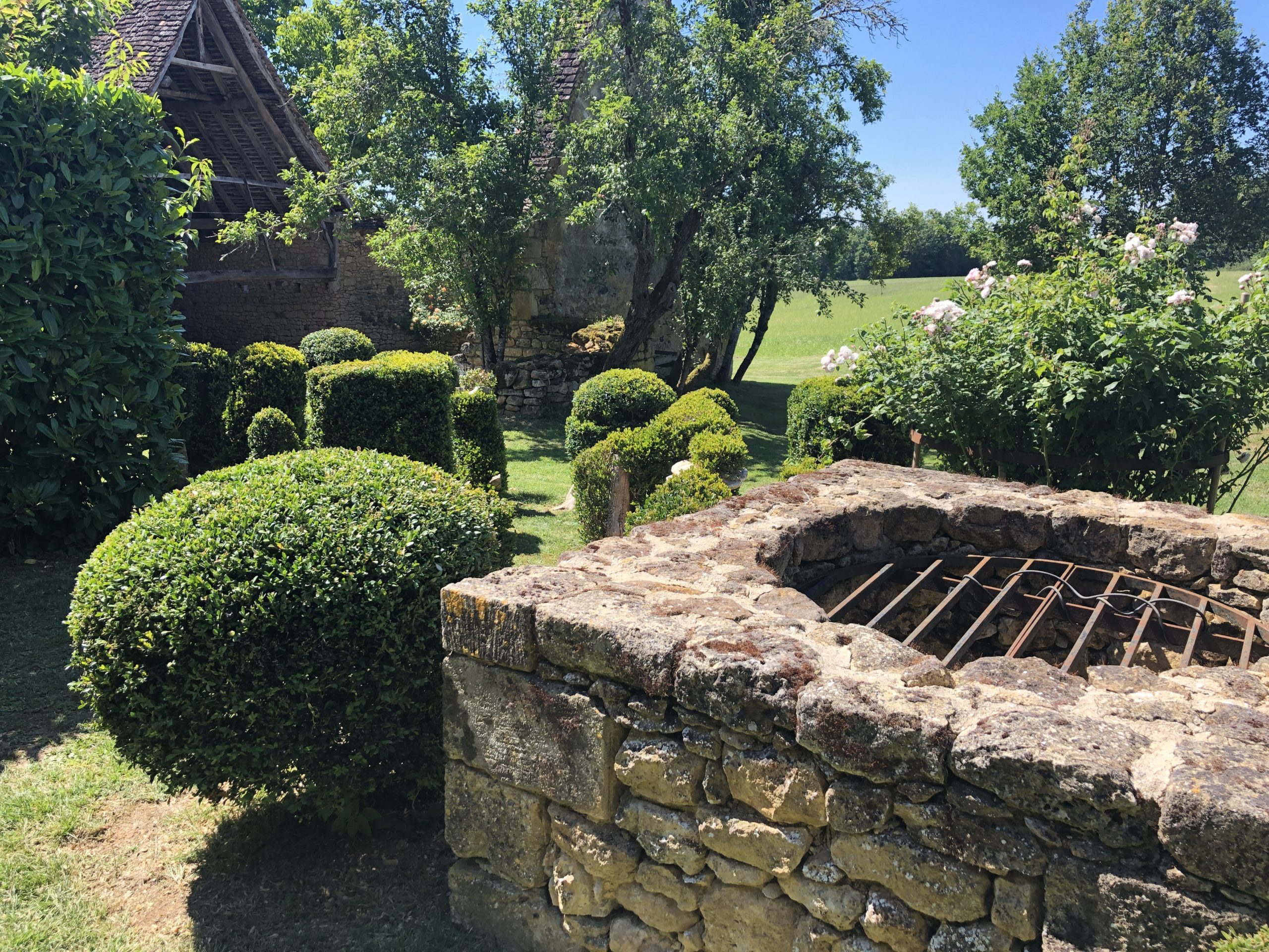 Luxury holiday accommodation in the Dordogne with an old stone well and topiary bushes in a beautiful garden