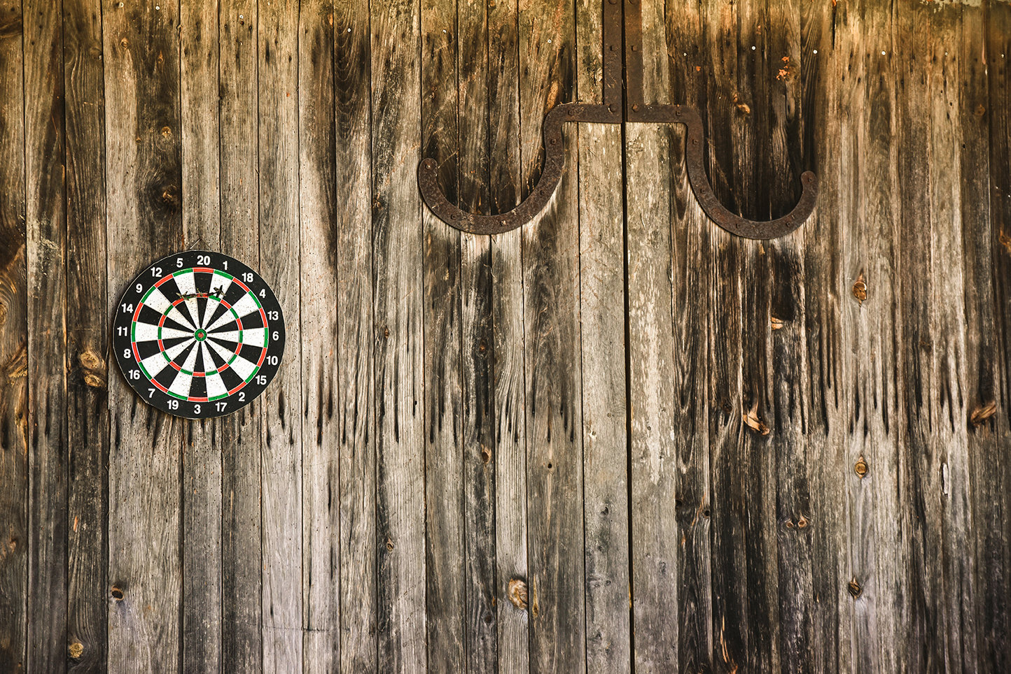 Group holiday accommodation in the Dordogne with a dartboard on an old wooden door in the games area