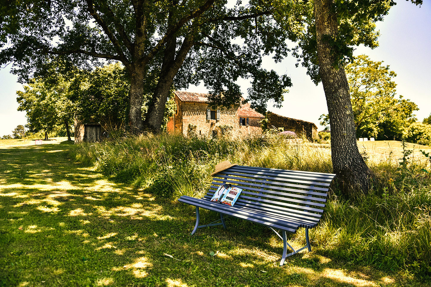 Tranquility on the sunset bench under oak trees in the garden of Le Mas & Le Mazet, vacation homes in the Dordogne