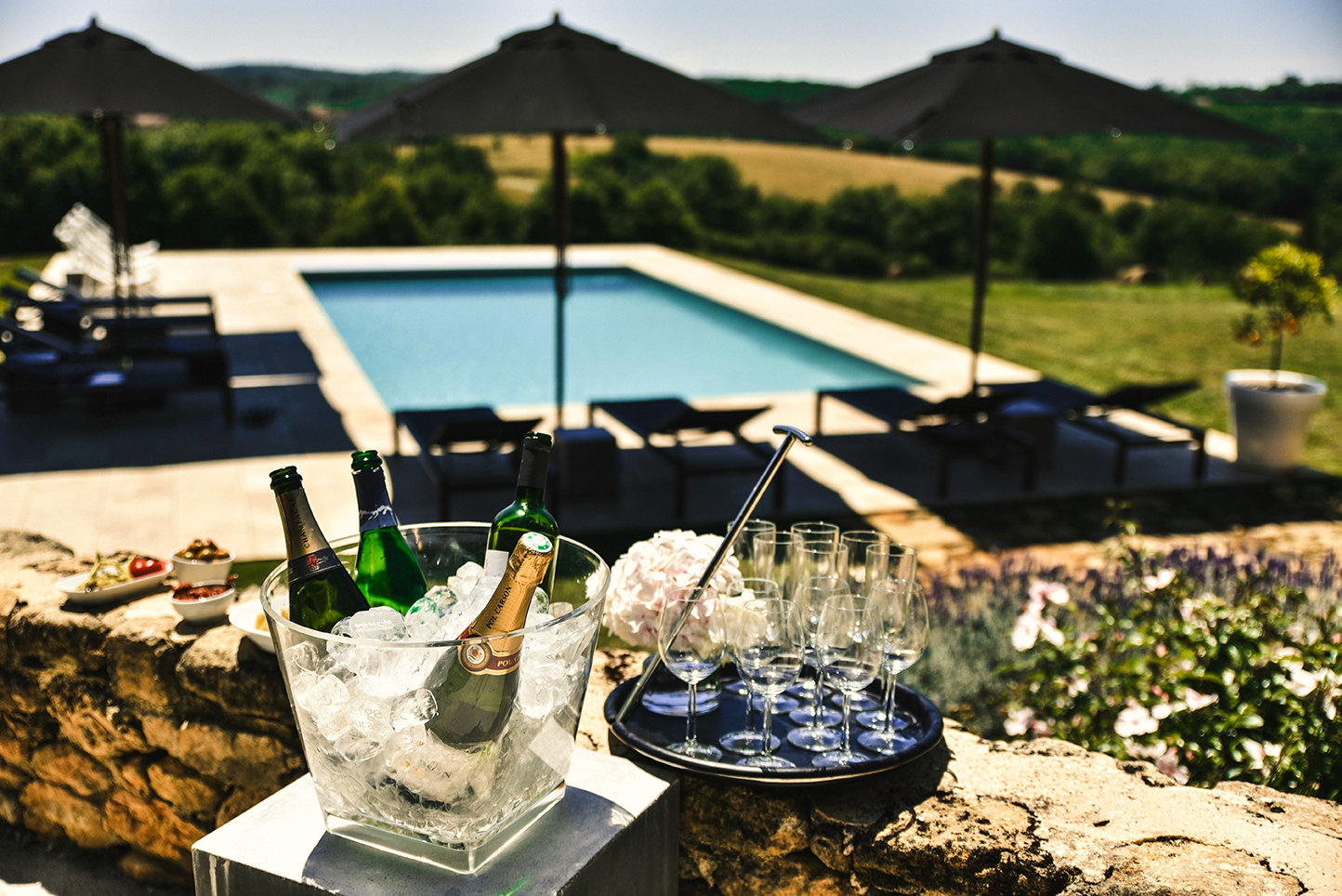 Apéritif on the terrace overlooking the pool at 5-star gites in the Dordogne with an ice-bucket filled with bottles, a tray of glasses and an amazing view over the private pool and the Périgrodine countryside beyond