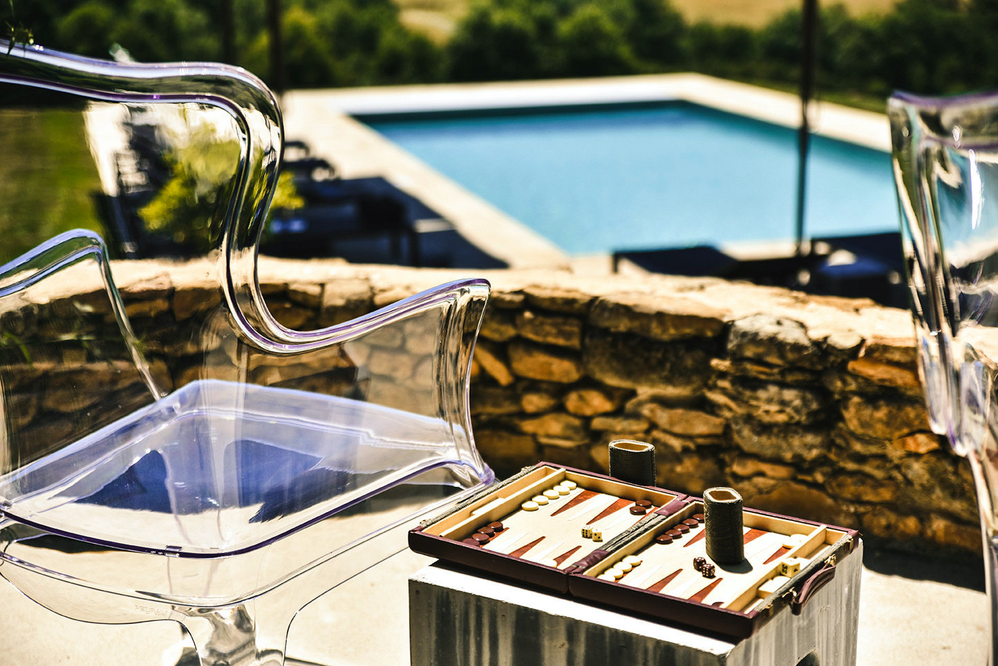 Perspex armchairs by Pedrali with a game of backgammon on a terrace overlooking a private pool and Dordogne countryside
