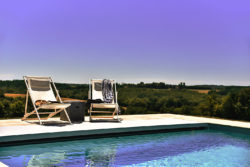 Saltwater pool with breathtaking views over the Dordogne countryside and two white deckchairs
