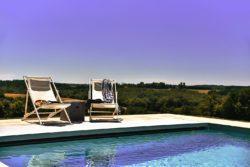 Zoutwaterzwembad met adembenemend uitzicht over het platteland van de Dordogne en twee witte ligstoelen