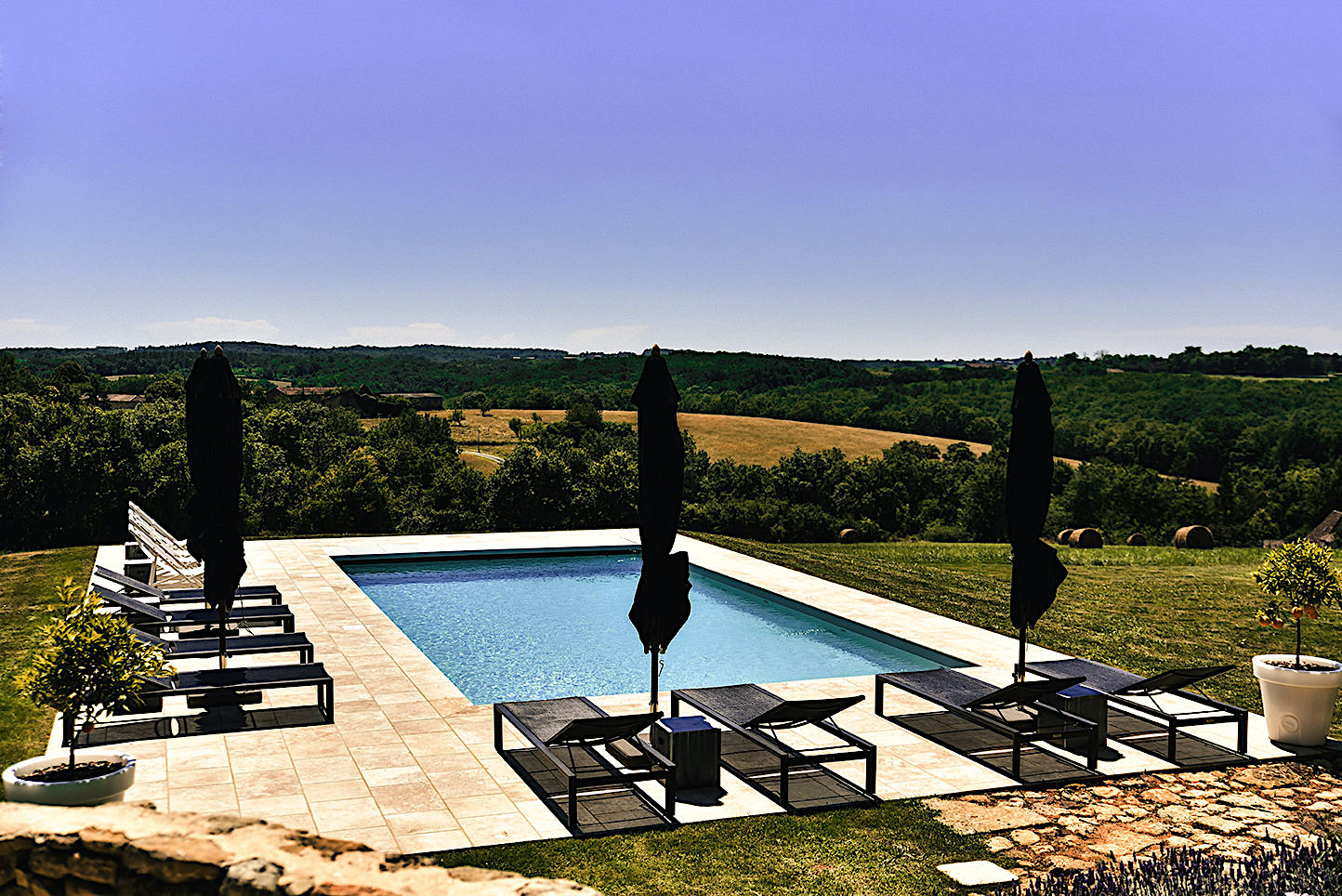 Blue saltwater pool in the garden of a luxury holiday home in the Dordogne, France, with black sun loungers and parasols and a view over the countryside