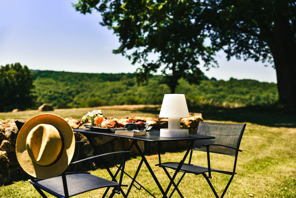A Fermob table and chairs laid for breakfast in a garden with a large oak tree and the Dordogne countryside