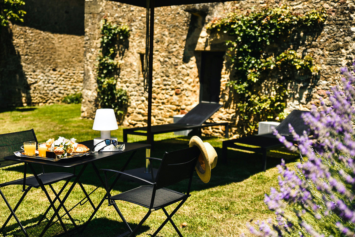 The private garden of a 1-bedroom holiday cottage in the Dordogne with garden furniture, lavender and roses climbing the stone walls