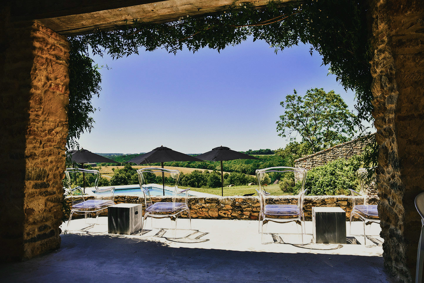 Luxury holiday accommodation in the Dordogne with a sun terrace with Pedrali chairs overlooking the countryside, framed by jasmine