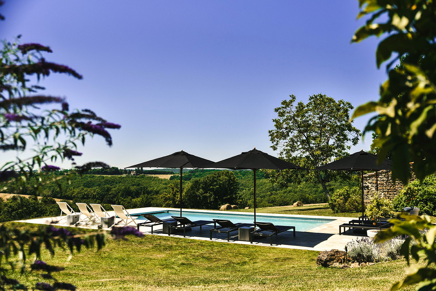 Family vacation rental in the Dordogne with saltwater swimming pool in the middle of the countryside with black sun loungers and parasols