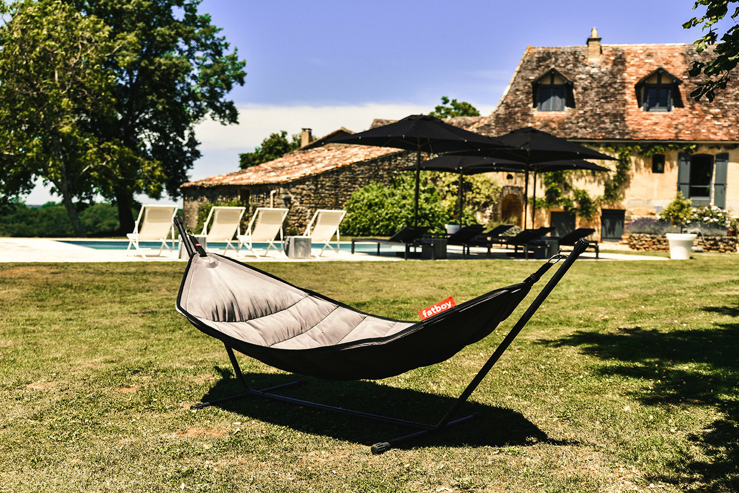 Stunning French holiday home with a black Fatboy double hammock on a lawn in front of a private pool and walnut tree