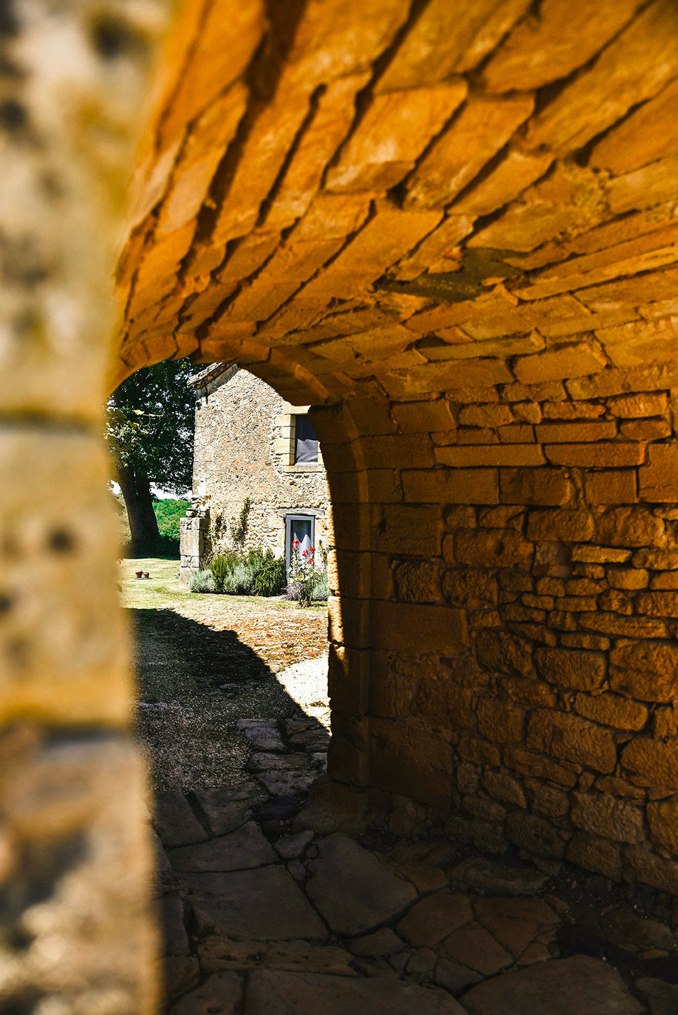 The centuries-old tunnel leading from Le Mas to Le Mazet in the Dordogne, France, with the holiday cottage in the sunlight in front of a large oak tree