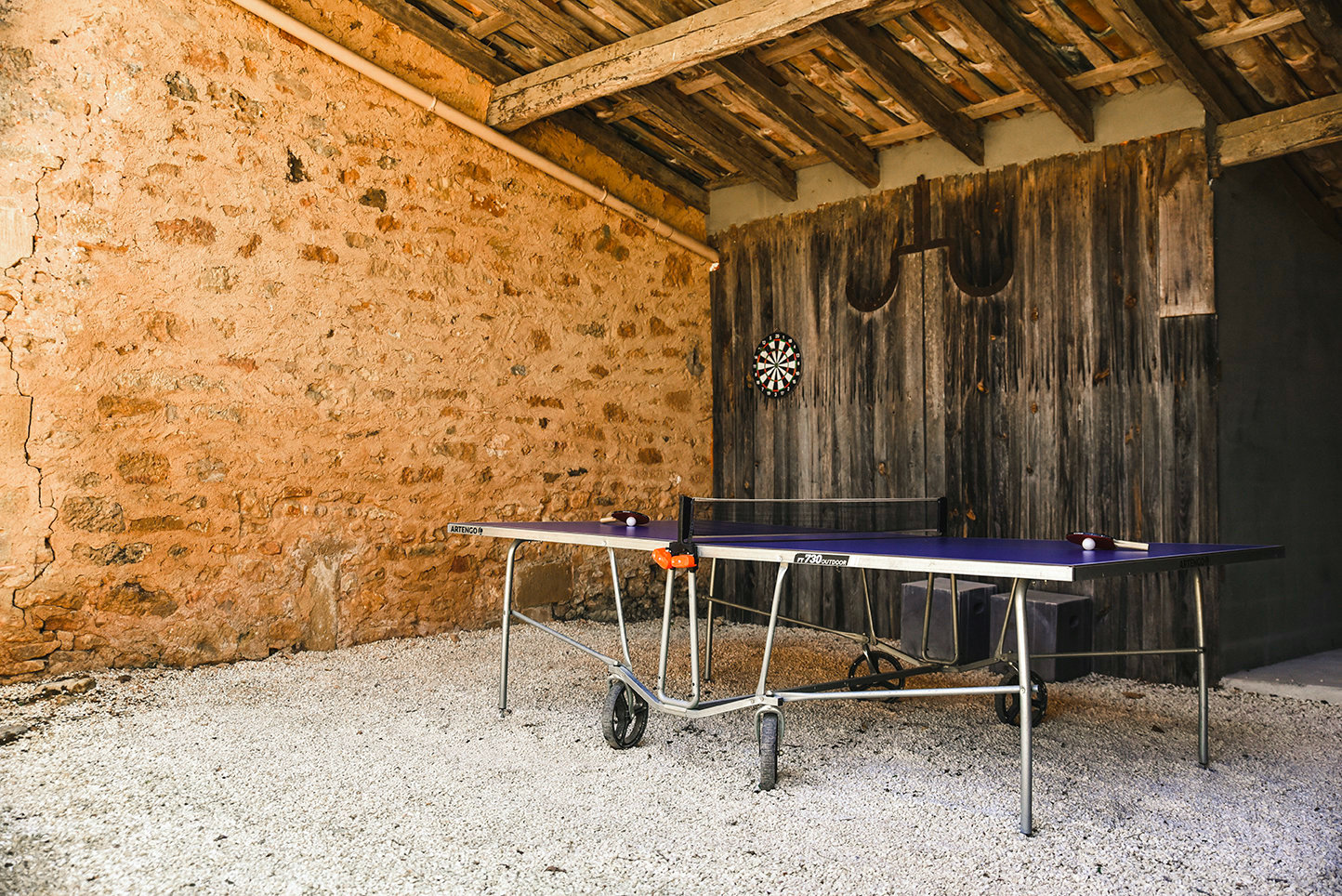 Luxury holiday house in the Dordogne, France, with a table tennis table in a stone and roofed open structure on white gravel
